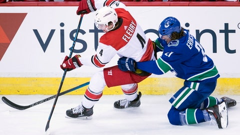 Vancouver Canucks left wing Loui Eriksson (21) competes for control of the puck with Carolina Hurricanes defenseman Haydn Fleury (4) during the third period of an NHL hockey game Tuesday, Dec. 5, 2017, in Vancouver, British Columbia. (Jonathan Hayward/The Canadian Press via AP)