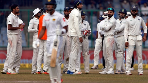 India's Ravichandran Ashwin, left, celebrates with teammates the dismissal of Sri Lanka's captain Dinesh Chandimal during the fifth day of their third test cricket match in New Delhi, India, Wednesday, Dec. 6, 2017. (AP Photo/Altaf Qadri)