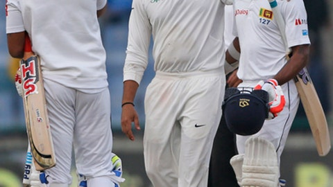India's Rohit Sharma, center, walks with Sri Lanka's Niroshan Dickwella at the end of third test cricket match against Sri Lanka in New Delhi, India, Wednesday, Dec. 6, 2017. (AP Photo/Altaf Qadri)