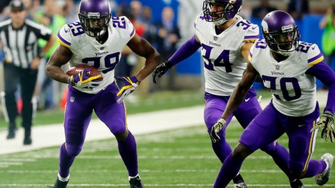 FILE- In this Thursday, Nov. 23, 2017, file photo, Minnesota Vikings cornerback Xavier Rhodes (29) returns an interception as teammates Mackensie Alexander (20) and Andrew Sendejo move into block during the second half of an NFL football game against the Detroit Lions in Detroit.  The Vikings let cornerback Captain Munnerlyn sign with the Carolina Panthers in free agency, but their pass coverage hasn't slipped with Rhodes, Alexander, Trae Waynes and Terence Newman helping to hold together a quality group.  (AP Photo/Rick Osentoski, File)