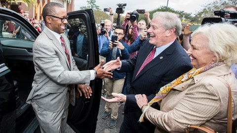 Willie Taggart, left, is greeted by Florida State University president John Thrasher and his wife, Jean, as he arrives to be introduced as the school's new NCAA college football head coach, in Tallahassee, Fla., Wednesday, Dec. 6, 2017. (AP Photo/Mark Wallheiser)