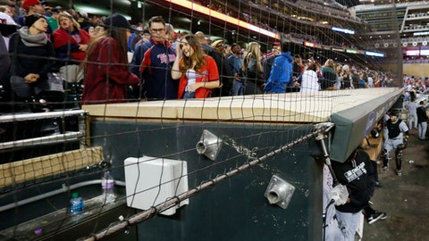 In this Wednesday, April 13, 2016 file photo, Minnesota Twins front row fans have protective netting to look through over the dugouts as they watch baseball games at Target Field where they took in the Twins and Chicago White Sox game in Minneapolis. The Cleveland Indians and Minnesota Twins are the latest Major League Baseball teams to announce plans for expansions of safety netting at their ballparks for the 2018 season. (AP Photo/Jim Mone, File)