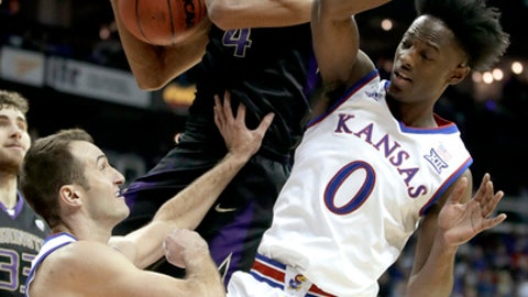 Washington's Matisse Thybulle, center, beats Kansas' Clay Young, left, and Marcus Garrett (0) to a rebound during the first half of an NCAA college basketball game Wednesday, Dec. 6, 2017, in Kansas City, Mo. (AP Photo/Charlie Riedel)