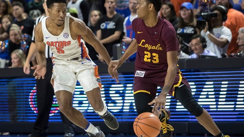 Loyola of Chicago guard Cameron Satterwhite (23) dribbles up the court against the defense of Florida guard KeVaughn Allen (5) during the second half of an NCAA college basketball game in Gainesville, Fla., Wednesday, Dec. 6, 2017. Loyola of Chicago won 65-59. (AP Photo/Ron Irby)