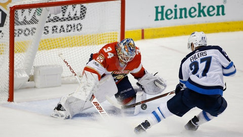 Winnipeg Jets left wing Nikolaj Ehlers (27) attempts a shot at Florida Panthers goalie James Reimer (34) during the second period of an NHL hockey game Thursday, Dec. 7, 2017, in Sunrise, Fla. (AP Photo/Wilfredo Lee)