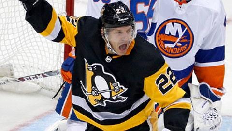 Pittsburgh Penguins' Matt Hunwick (22) celebrates his overtime goal in an NHL hockey game, against New York Islanders goalie Jaroslav Halak, right, and defender Joshua Ho-Sang (66) in Pittsburgh, Thursday, Dec. 7, 2017. The Penguins won 4-3. (AP Photo/Gene J. Puskar)