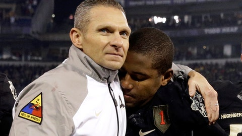 FILE - In this Dec. 13, 2014, file photo, Army head coach Jeff Monken, left, embraces running back Larry Dixon after losing 17-10 to Navy in an NCAA college football game, in Baltimore. Monken's second season at Army in 2015 ended with 10 losses and a record 14th straight defeat to Navy. While it pointed to more of the same for a struggling program, Monken was confident a West Point turnaround was imminent thanks to successful recruiting and the number of close losses. Monken was proven right.  (AP Photo/Patrick Semansky, File)