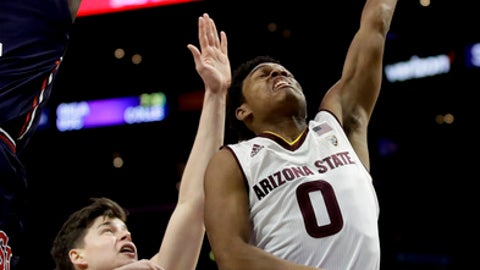 Arizona State guard Tra Holder, right, shoots over St. John's forward Amar Alibegovic during the first half of an NCAA college basketball game in Los Angeles, Friday, Dec. 8, 2017. (AP Photo/Chris Carlson)