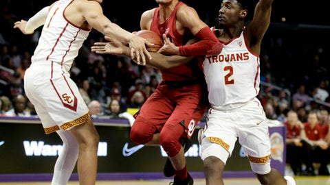 Oklahoma guard Trae Young, middle, drives between Southern California guards Jordan Usher, left, and Jonah Mathews during the first half of an NCAA college basketball game in Los Angeles, Friday, Dec. 8, 2017. (AP Photo/Chris Carlson)
