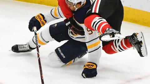 Chicago Blackhawks defenseman Connor Murphy falls onto Buffalo Sabres left wing Evander Kane (9) during the third period of an NHL hockey game Friday Dec. 8, 2017, in Chicago. (AP Photo/Matt Marton)