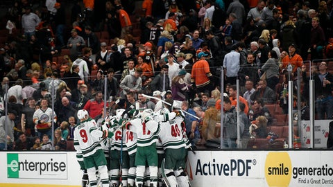 The Minnesota Wild celebrate a goal by defenseman Matt Dumba during overtime of an NHL hockey game against the Anaheim Ducks in Anaheim, Calif., Friday, Dec. 8, 2017. The Wild won 3-2. (AP Photo/Kelvin Kuo)