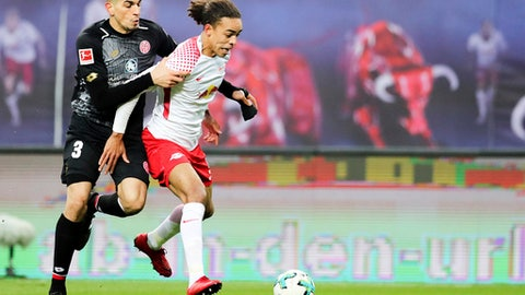 Leipzigs Yussuf Poulsen, right, and Mainz' Leon Balogun challenge for the ball during the German Bundesliga soccer match between RB Leipzig and FSV Mainz 05 at the Red Bull Arena in Leipzig, Germany, Saturday, Dec. 9, 2017. (Jan Woitas/dpa via AP) via AP)