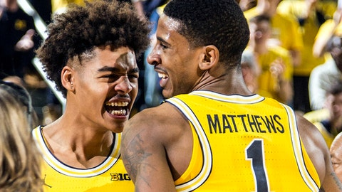 Michigan guard Jordan Poole, left, celebrates with guard Charles Matthews (1) during a timeout in overtime of an NCAA college basketball game at Crisler Center in Ann Arbor, Mich., Saturday, Dec. 9, 2017. Michigan won 78-69 in overtime. (AP Photo/Tony Ding)