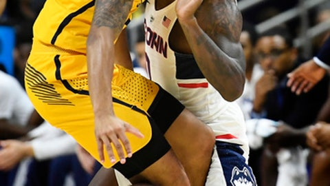 Coppin State's Tre' Thomas, left, is guarded by Connecticut's Antwoine Anderson, right, during the first half of an NCAA college basketball game, Saturday, Dec. 9, 2017, in Storrs, Conn. (AP Photo/Jessica Hill)
