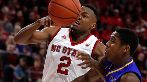 UMKC's Marvin Nesbitt Jr. (33) fouls N.C. State's Torin Dorn (2) during the first half of N.C. State's game against the University of Missouri-Kansas City at Reynolds Coliseum in Raleigh, N.C., Saturday, Dec. 9, 2017. (Ethan Hyman/The News & Observer via AP)