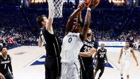 Xavier's Tyrique Jones (0) shoots against Colorado's Lazar Nikolic (11) and Dallas Walton (35) in the first half of an NCAA college basketball game, Saturday, Dec. 9, 2017, in Cincinnati. (AP Photo/John Minchillo)