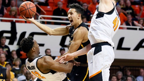 Wichita State guard Landry Shamet, center, is fouled by Oklahoma State forward Cameron McGriff (12) as he shoots between McGriff and forward Mitchell Solomon (41) in the second half of an NCAA college basketball game in Stillwater, Okla., Saturday, Dec. 9, 2017 (AP Photo/Sue Ogrocki)