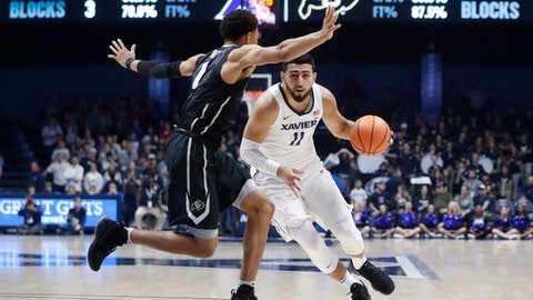Xavier's Kerem Kanter (11) drives against Colorado's Tyler Bey (1) in the second half of an NCAA college basketball game, Saturday, Dec. 9, 2017, in Cincinnati. (AP Photo/John Minchillo)