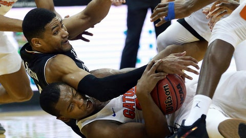 Florida's Keith Stone, bottom, tries to hold onto the ball as Cincinnati's Kyle Washington tries to make a steal during the first half of an NCAA college basketball game Saturday, Dec. 9, 2017, in Newark, N.J. (AP Photo/Mel Evans)