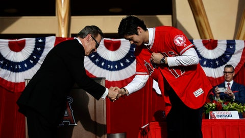 Baseball player Shohei Ohtani, right, of Japan, shakes hands with Los Angeles Angels owner Arte Moreno as he puts on his jersey during a news conference at Angel Stadium, Saturday, Dec. 9, 2017, in Anaheim, Calif. Ohtani is bringing his arm and bat to the Angels, pairing him with two-time MVP Mike Trout. (AP Photo/Jae C. Hong)