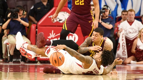 Minnesota guard Nate Mason, right, and Arkansas guard Anton Beard, left, fall to the ground as they go after a loose ball in the second half of an NCAA college basketball game Saturday, Dec. 9, 2017 in Fayetteville, Ark. (AP Photo/Michael Woods)