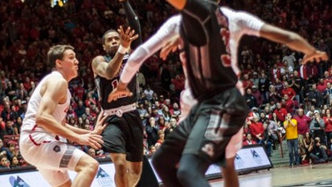 New Mexico State's AJ Harris (12) makes a pass to teammate Johnny McCants, foreground, while guarded by New Mexico's Joe Furstinger, left, during the first half of an NCAA college basketball game in Albuquerque, N.M., Saturday, Dec. 9, 2017. (AP Photo/Juan Antonio Labreche)