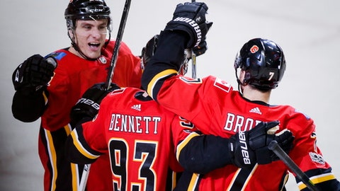 Calgary Flames' Sam Bennett, center, celebrates his goal with teammates Garnet Hathaway, left, and T.J. Brodie against the Vancouver Canucks during the third period of an NHL hockey game Saturday, Dec. 9, 2017, in Calgary, Alberta. (Jeff McIntosh/The Canadian Press via AP)