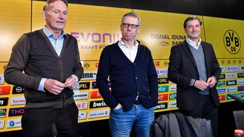 Borussia Dortmund CEO Hans-Joachim Watzke, left, and sporting manager Michael Zorc, right, present Austrian coach Peter Stoeger, center, as the new head coach of the Bundesliga soccer club at a press conference in Dortmund, Germany, Sunday, Dec. 10, 2017. Borussia Dortmund displaced Dutch head coach Peter Bosz on Saturday after a defeat against Werder Bremen. Stoeger was dismissed as head coach of FC Cologne earlier this month. (AP Photo/Martin Meissner)