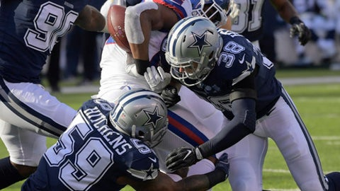 New York Giants running back Wayne Gallman (22) fumbles the ball as he is hit by Dallas Cowboys strong safety Jeff Heath (38) and Dallas Cowboys middle linebacker Anthony Hitchens (59) during the first quarter of an NFL football game, Sunday, Dec. 10, 2017, in East Rutherford, N.J. (AP Photo/Bill Kostroun)