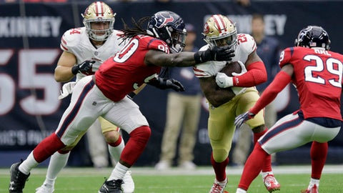 San Francisco 49ers running back Carlos Hyde (28) is grabbed by Houston Texans outside linebacker Jadeveon Clowney (90) during the first half of an NFL football game, Sunday, Dec. 10, 2017, in Houston. (AP Photo/Michael Wyke)