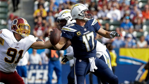 Los Angeles Chargers quarterback Philip Rivers throws a pass under pressure from Washington Redskins linebacker Ryan Kerrigan (91) during the first half of an NFL football game Sunday, Dec. 10, 2017, in Carson, Calif. (AP Photo/Alex Gallardo)