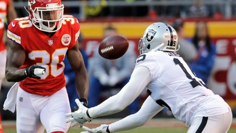 Oakland Raiders wide receiver Michael Crabtree (15) attempts to catch the ball after it deflected off the arm of Kansas City Chiefs defensive back Steven Terrell (30) during the second half of an NFL football game in Kansas City, Mo., Sunday, Dec. 10, 2017. Crabtree did not catch the ball. (AP Photo/Charlie Riedel)