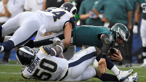 Philadelphia Eagles quarterback Carson Wentz, right, is tackled by Los Angeles Rams linebacker Samson Ebukam (50) and inside linebacker Bryce Hager during the second half of an NFL football game Sunday, Dec. 10, 2017, in Los Angeles. (AP Photo/Mark J. Terrill)
