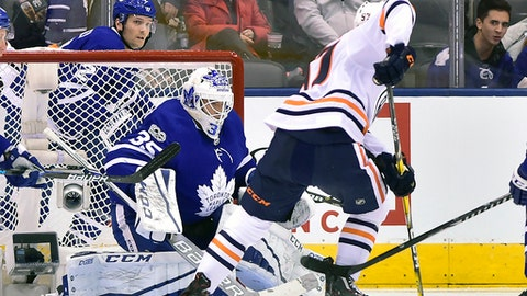 Toronto Maple Leafs goalie Curtis McElhinney (35) makes a save against Edmonton Oilers center Connor McDavid (97) during second-period NHL hockey game action in Toronto, Sunday, Dec. 10, 2017. (Frank Gunn/The Canadian Press via AP)