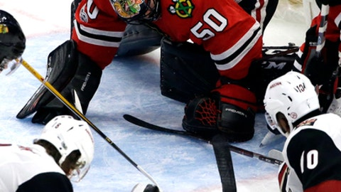 Chicago Blackhawks goalie Corey Crawford (50)  stops a shot from the Arizona Coyotes during the third period of an NHL hockey game Sunday, Dec. 10, 2017, in Chicago. (AP Photo/Nam Y. Huh)
