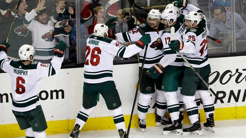 Minnesota Wild's Nino Niederreiter (22), center, is mobbed by teammates after his game-winning goal during overtime of an NHL hockey game against the San Jose Sharks, Sunday, Dec. 10, 2017, in San Jose, Calif. Minnesota won 4-3. (AP Photo/Marcio Jose Sanchez)