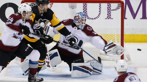 Colorado Avalanche goalie Jonathan Bernier, center, reaches for a shot wide of the net with teammate Anton Lindholm (54) defending against Pittsburgh Penguins' Bryan Rust, second from left, during the third period of an NHL hockey game in Pittsburgh, Monday, Dec. 11, 2017. (AP Photo/Gene J. Puskar)