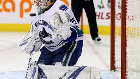 Vancouver Canucks goalie Jacob Markstrom (25) has a puck come near his chin during second-period NHL hockey game action against the Winnipeg Jets in Winnipeg, Manitoba, Monday, Dec. 11, 2017. (Trevor Hagan/The Canadian Press via AP)