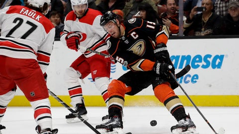 Anaheim Ducks center Ryan Getzlaf, right, knocks the puck away from Carolina Hurricanes defenseman Justin Faulk, left, and center Marcus Kruger during the second period of an NHL hockey game in Anaheim, Calif., Monday, Dec. 11, 2017. Getzlaf missed the last 19 games due to a facial fracture. (AP Photo/Chris Carlson)