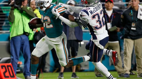 New England Patriots free safety Devin McCourty (32) attempts to stop Miami Dolphins running back Kenyan Drake (32), during the second half of an NFL football game, Monday, Dec. 11, 2017, in Miami Gardens, Fla. Drake had 114 yards rushing and 79 receiving during the game.(AP Photo/Wilfredo Lee)
