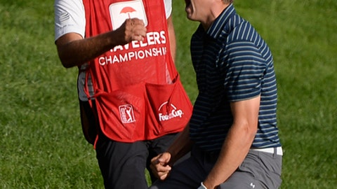 FILE - In this June 25, 2017, file photo, Jordan Spieth celebrates with caddy Michael Greller after sinking a shot from a bunker on the first playoff hole during the final round of the Travelers Championship golf tournament, in Cromwell, Conn. Spieth's bunker shot was the most memorable with a lob wedge. (AP Photo/Jessica Hill, File)