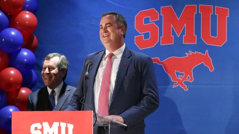 New SMU head NCAA college football coach Sonny Dykes, right, laughs with university president Gerald Turner after Dykes introduction in Dallas, Tuesday, Dec. 12, 2017. SMU hired the former California and Louisiana Tech coach as its new coach, replacing one Texan with reputation for directing potent offenses for another. Dykes will replace Chad Morris, who left SMU last week to become Arkansas' coach. (AP Photo/LM Otero)