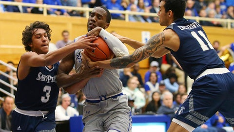 Seton Hall's Khadeen Carrington, center fights off St. Peter's Elijah Gonzales (3) and Nnamdi Enechionyia (11) as he charges the basket during the first half of an NCAA college basketball game in South Orange, N.J., Tuesday, Dec. 12, 2017. (AP Photo/Rich Schultz)