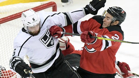 New Jersey Devils defenseman John Moore (2) checks Los Angeles Kings defenseman Jake Muzzin (6) during the third period of an NHL hockey game Tuesday, Dec.12, 2017, in Newark, N.J. The Devils won 5-1. (AP Photo/Bill Kostroun)