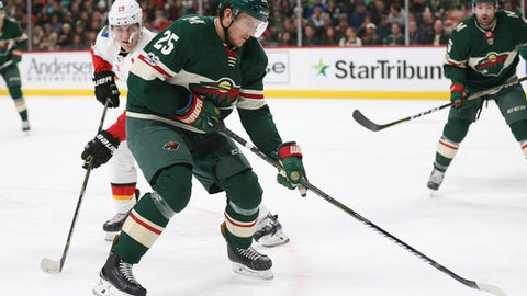 Minnesota Wild's Jonas Brodin (25) controls the puck in front of Calgary Flames' Matthew Tkachuk (19) in the second period of an NHL hockey game Tuesday, Dec. 12, 2017, in St. Paul, Minn. (AP Photo/Stacy Bengs)