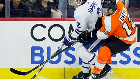Toronto Maple Leafs' Ron Hainsey, left, takes control of the puck away from the Philadelphia Flyers' Michael Raffl during the second period of an NHL hockey game, Tuesday, Dec. 12, 2017, in Philadelphia. The Flyers won 4-2. (AP Photo/Tom Mihalek)