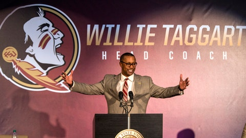 FILE - In this Dec. 6, 2017, file photo, Willie Taggart gestures as he is introduced as Florida State's new football coach during an NCAA college football news conference in Tallahassee, Fla. A potential new tax on seven-figure salaries for employees of non-profits hasn't deterred schools from doling out huge contracts to new coaches. (AP Photo/Mark Wallheiser, File)