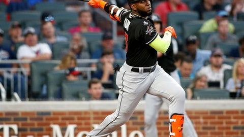 FILE - In this Sept. 7, 2017, file photo, Miami Marlins' Marcell Ozuna watches his RBI triple during the first inning of a baseball game against the Atlanta Braves, in Atlanta. A person familiar with the negotiations says Miami has agreed to trade left fielder Marcell Ozuna to the St. Louis Cardinals, the third All-Star jettisoned by the Marlins this month in an unrelenting payroll purge under new CEO Derek Jeter. The person spoke to The Associated Press on condition of anonymity Wednesday because the agreement had not been announced and was subject to a physical. (AP Photo/Brett Davis, File)