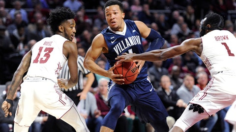 Villanova's Jalen Brunson (1) drives to the basket against Temple's Quinton Rose (13) and Josh Brown (1) during the first half an NCAA college basketball game, Wednesday, Dec. 13, 2017, in Philadelphia. (AP Photo/Michael Perez)