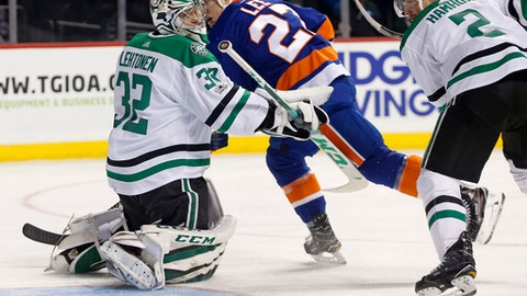 New York Islanders left wing Anders Lee (27) watches his shot slip through the crease behind Dallas Stars goalie Kari Lehtonen (32) of Finland during the second period of an NHL hockey game in New York, Wednesday, Dec. 13, 2017. Dallas Stars defenseman Dan Hamhuis (2) watches, right. (AP Photo/Kathy Willens)